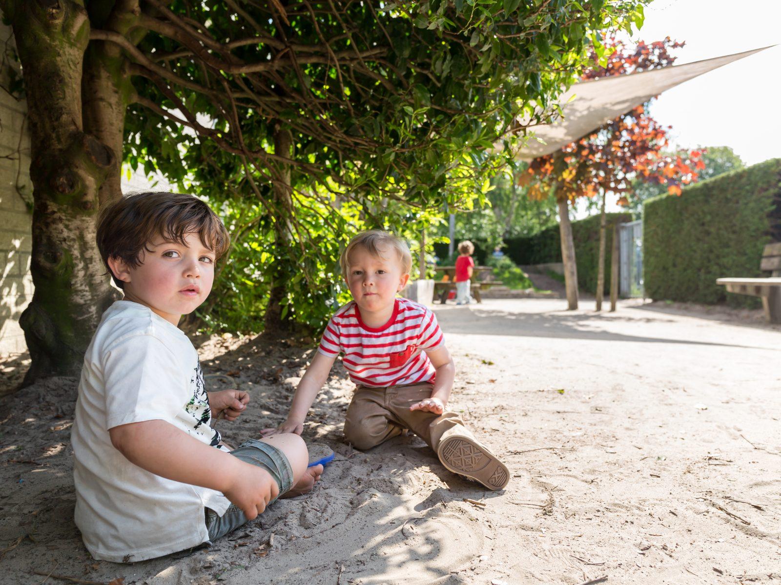 Ons aanbod: Twee jongetjes spelen buiten in het zand