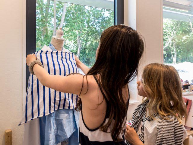 Meisjes kleden een paspop aan